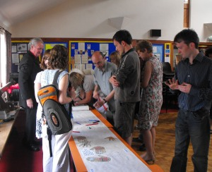 Parishioners create their climate banner under the watchful eye of Jim O'Neill, Parish Contact (left)