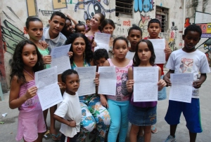 Nete, Maua´s community leader (centre), with children, holding petitions signed by parishioners from England and Wales, campaigning against an earlier eviction threat.